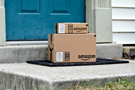 consumerism: MARYLAND, USA - JANUARY 18, 2016: Image of Amazon packages delivered to a home. Amazon is the largest internet based retailer in the United States.