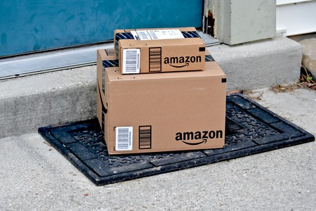 doorstep: MARYLAND, USA - JANUARY 18, 2016: Image of Amazon packages delivered to a home. Amazon is the largest internet based retailer in the United States.
