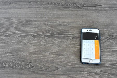 MARYLAND, USA - APRIL 3, 2016: An Apple iPhone 6s displaying the calculator app on a wood surface. The iPhone is a popular product manufactured by Apple Inc.
