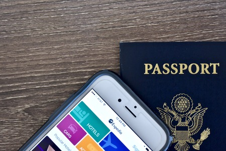 MARYLAND, USA - APRIL 3, 2016: An Apple iPhone 6s displaying the Expedia application homepage on the screen while laying next to an American passport. The iPhone is a product of Apple Inc. Editorial