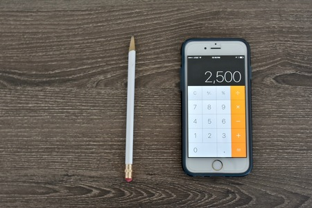 MARYLAND, USA - APRIL 10, 2016: An Apple iPhone 6s displaying the calculator application while laying on a wood surface. The Apple iPhone 6s is a product of Apple Inc. Editorial