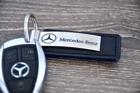 10 key: MARYLAND, USA - APRIL 10, 2016: A Mercedes-Benz key fob laying on a wood surface. Mercedes-Benz is a luxury car manufacturer and dealer.