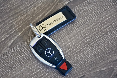key fob: MARYLAND, USA - APRIL 10, 2016: A Mercedes-Benz key fob laying on a wood surface. Mercedes-Benz is a luxury car manufacturer and dealer.