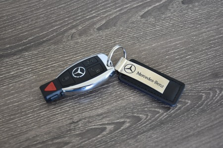 fob: MARYLAND, USA - APRIL 10, 2016: A Mercedes-Benz key fob laying on a wood surface. Mercedes-Benz is a luxury car manufacturer and dealer.