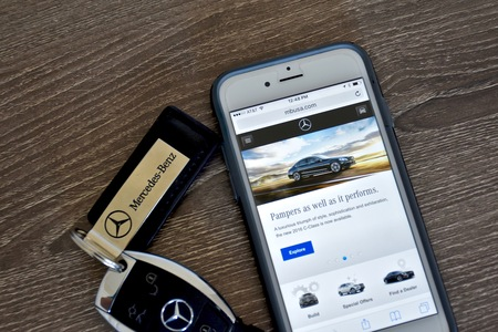 10 key: MARYLAND, USA - APRIL 10, 2016: An Apple iPhone 6S displaying the Mercedes-Benz web page while laying next to a Mercedes-Benz key fob. Editorial