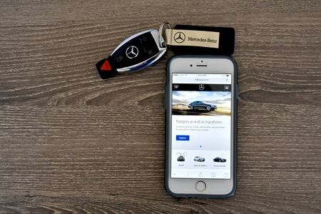 fob: MARYLAND, USA - APRIL 10, 2016: An Apple iPhone 6S displaying the Mercedes-Benz web page while laying next to a Mercedes-Benz key fob. Editorial