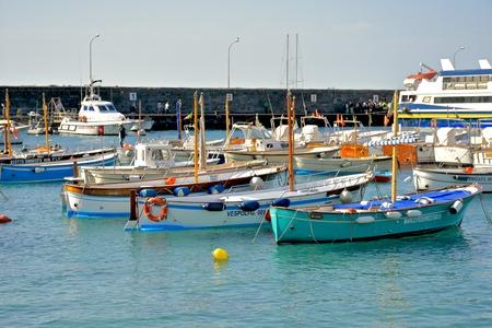 capri: CAPRI, ITALY - APRIL 16, 2016: Boats docked near the shore of Capri island. Capri is and island of Italy.