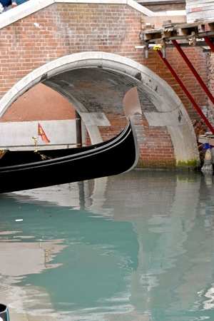 venician: Gondola coming out from under a bridge