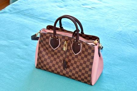 designer bag: SORRENTO, ITALY - APRIL 20, 2016: A Louis Vuitton handbag on a blue bed sheet.