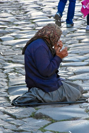 tourist destination: ROME, ITALY - APRIL 15, 2016: A homeless lady begging for money in Rome. Rome is a popular tourist destination in Italy.