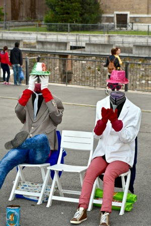 tourist destination: ROME, ITALY - APRIL 16, 2015: Two mimes hiding their faces while performing acts in Rome. Rome is a popular tourist destination in Italy.