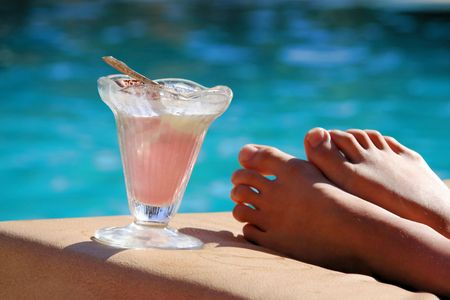 Girl resting at the edge of the swimming pool with an ice cream
