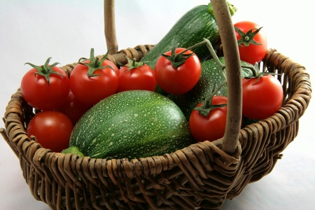 Basket of tomatoes and zucchinis in close-up photo