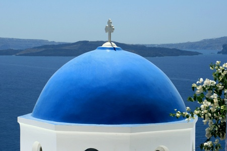 Church in the blue roof to Santorin-Santorini on the background of blue sky photo
