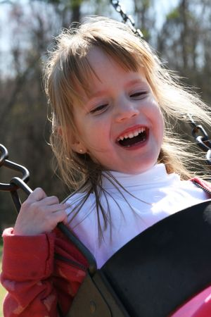 absorbed: 4 year old girl on the swing Stock Photo