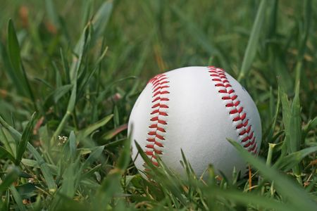 Lonely baseball in the grass photo
