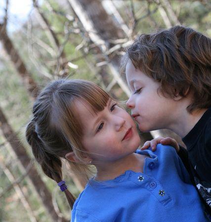 Boy kissing his sister photo