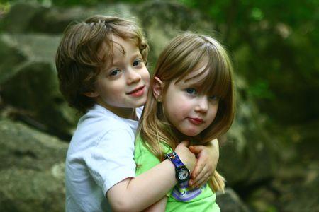2 children sitting by a creek