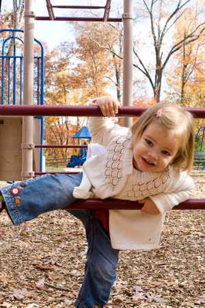 A little girl on the playground on an autumn day Imagens