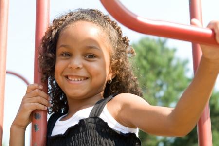 Een mooi gemengd ras kind genieten van de speeltuin Stockfoto
