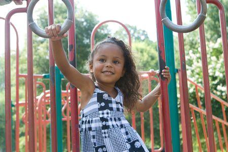 A beautiful mixed race child enjoying the playground photo
