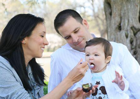 Mom and dad feeding their infant a healthy avacado snack photo