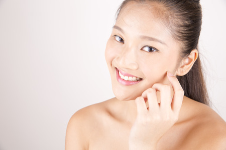 Asian young beautiful smiling woman with flawless complexion touching face