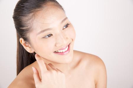 Belle jeune femme souriante asiatique avec teint impeccable toucher le visage avec les deux mains