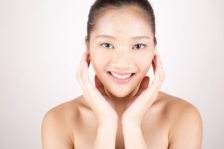 Asian young beautiful smiling woman with flawless complexion touching face with both hands