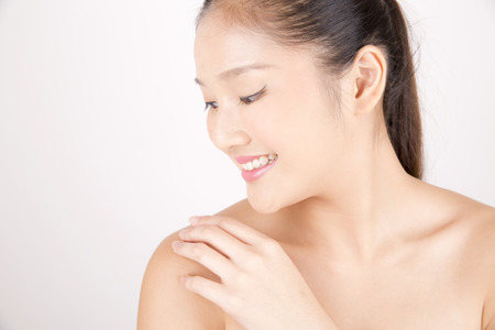 Asian young beautiful smiling woman with flawless complexion touching shoulder