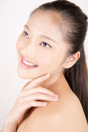 fair complexion: Asian young beautiful smiling woman with flawless complexion touching face