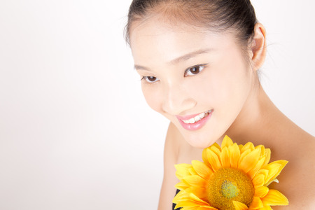 fair complexion: Asian young beautiful smiling woman with flawless complexion with bright sunflower