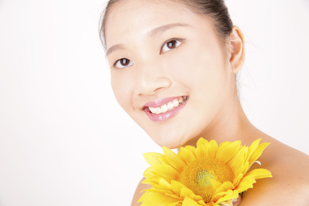 Asian young beautiful smiling woman with flawless complexion with bright sunflower
