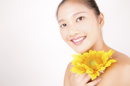 Belle jeune femme souriante asiatique avec teint impeccable avec tournesol lumineux