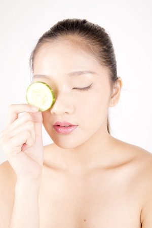 Asian young beautiful woman with flawless complexion holding cucumber slice over eye Stock Photo