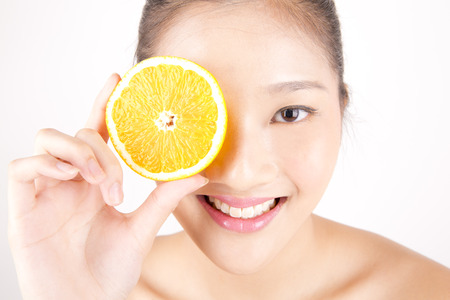 Asian young beautiful smiling woman with flawless complexion holding orange slice over eye