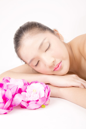 Asian young beautiful woman with flawless complexion with red peony flowers relaxing
