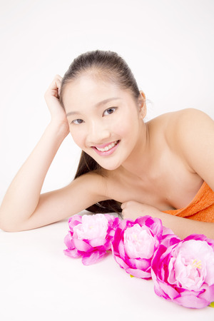Jeune asiatique belle femme au teint impeccable souriant avec des fleurs de pivoine rouge d�tente