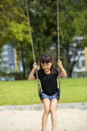 Jeune fille asiatique dans le parc swing de jeu Banque d'images