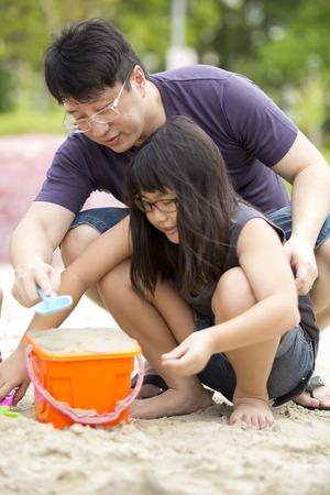 Jeune famille asiatique � jouer sable dans le parc