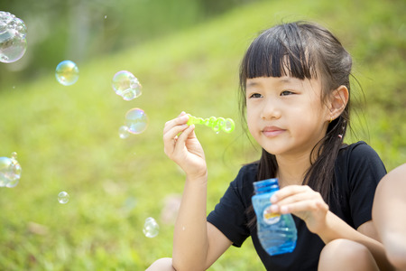 girl blowing: Young Asian girl blowing bubbles in park Stock Photo
