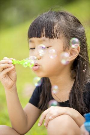 Jeune fille asiatique soufflant des bulles dans le parc Banque d'images