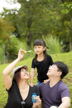 blowing bubbles: Young Asian family blowing bubbles in park