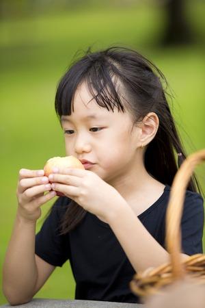 Asie jeune fille de manger l'orange dans le parc Banque d'images