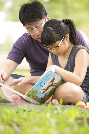 Young Asian family reading in park photo