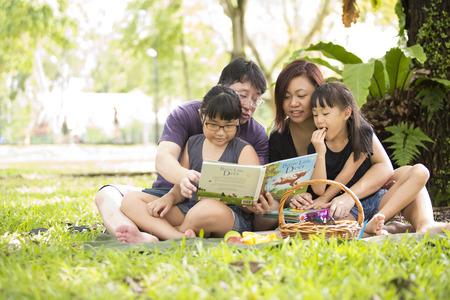 公園で本を読んで若いアジア家族
