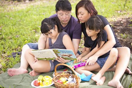 Young Asian family reading in park Stock Photo