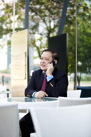 D'affaires asiatique parlant sur t�l�phone intelligent Banque d'images