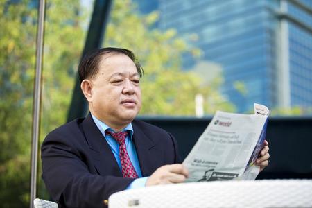real leader: Asian businessman reading newspaper