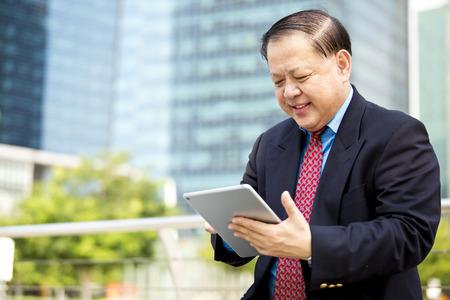 liderazgo empresarial: Hombre de negocios asiático que usa la tableta Foto de archivo